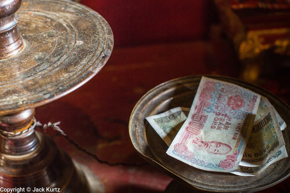 02 APRIL 2012 - HANOI, VIETNAM: Money left as a donation in Ngoc Son Temple, which was reportedly built during the Tran Dynasty (ca 1225) in the Old Quarter of Hanoi, Vietnam. The temple is dedicated to Tran Hung Dao, a Vietnamese national hero who defeated an invading Mongol army in the 13th century.    PHOTO BY JACK KURTZ