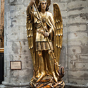 A statue of St Michel (St Michael), one of the church's patron saints, at the Cathedral of St. Michael and St. Gudula (in French, Co-Cathédrale collégiale des Ss-Michel et Gudule). A church was founded on this site in the 11th century but the current building dates to the 13th to 15th centuries. The Roman Catholic cathedral is the venue for many state functions such as coronations, royal weddings, and state funerals. It has two patron saints, St Michael and St Gudula, both of whom are also the patron saints of Brussels.