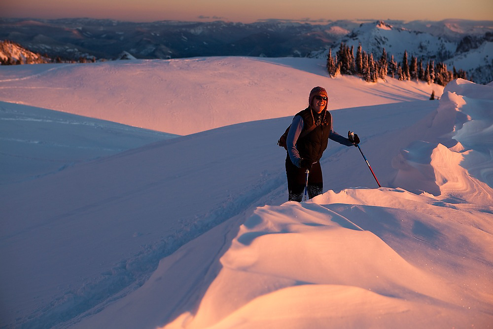 Julia Wentzel laughs as she ascends a windswept ridge at sunset above Paradise in Mount Rainier National Park.