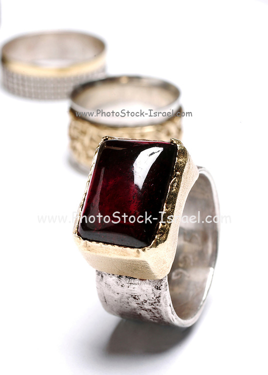 Ruby on a silver ring on white background with wedding rings in the background