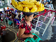 20 NOVEMBER 2017 - YANGON, MYANMAR: A pineapple vendor on the Dala Ferry. There are vendors selling fruit, snacks, betel, toys, and phone SIM cards on the ferry. People getting off the Dala Ferry in Yangon leave the ferry terminal. Tens of thousands of commuters ride the ferry every day. It brings workers into Yangon from Dala, a working class community across the river from Yangon. A bridge is being built across the river, downstream from the ferry to make it easier for commuters to get into the city.     PHOTO BY JACK KURTZ