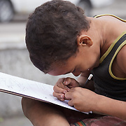 A young boy drawing on the streets of Havana, Cuba.