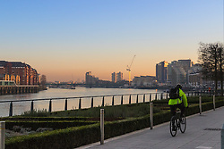 London, February 24th 2016. A cyclist rides along the Thames as the sun rises on a chilly but clear morning in London. ©Paul Davey<br /> FOR LICENCING CONTACT: Paul Davey +44 (0) 7966 016 296 paul@pauldaveycreative.co.uk