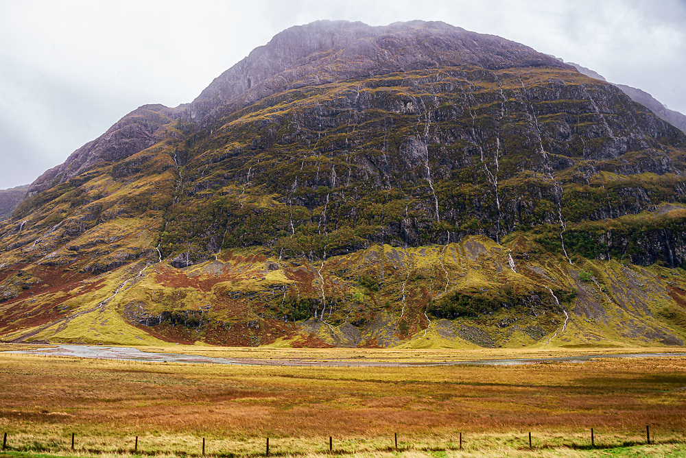 Ossian, a mythical entity of Scottish and Irish lore that was betimes a stag, otherwise human of sorts, reputedly inhabited the apparent cave seen here high on Aonach Dubh. Run-off from heavy rains cascade down the mountainside.