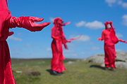 Spectacularly costumed Red Rebels perform an action near Lands end in Cornwall on 15th May 2020 in Carn Les Boel, United Kingdom. They walked to the cliff tops and stood like statues in protest against rising sea levels. As a group they protest against climate change, often with Extinction Rebellion. Their bright red costumes symbolises the common blood they share. They stand as living statues. These protests are highlighting that the government is not doing enough to avoid catastrophic climate change and to demand the government take radical action to save the planet.