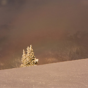 A clearing winter storm produces a rainbow at sunset in Vail, Colorado.