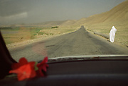On the road to the Wakhan Corridor, near the city of Pul-i-Kumbri. A woman wearing a white Burka waiting to get a ride.