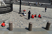 Wearing red school uniform jumpers, a group of schoolchildren enjoy warm sunshine during a day of outdoor learning in St Paul's Cathedral churchyard in the City of London, the capital's financial district, on 23rd June 2021, in London, England.