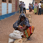 An old woman securely fastens her bag of relief food during the East African drought. Wajir, North Eastern Province, Kenya.