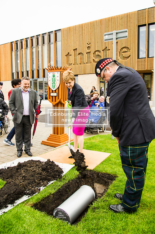 Pictured: Nicola Sturgeon braves the showers to bury the time capsule<br /> <br /> The First Minister Nicola Sturgeon, MSP, joined people supported by the Thistle Foundation to bury a time capsule to mark the opening of a new health and social care centre. <br /> Ger Harley   EEm 14 June 2016