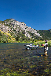 """Flyfisherman, John Rennell trying his luck on the Southfork of the Snake River near Swan Valley, Idaho.  The iconic """"hole in the wall"""" towering above."""