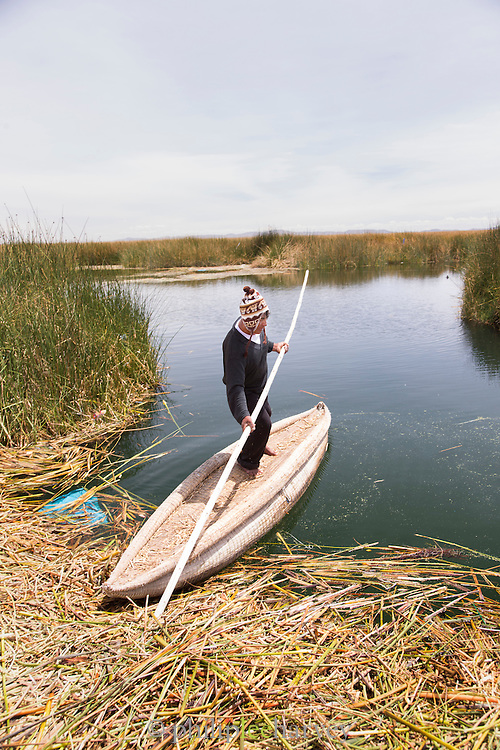 Native Uru man off to catch fish on a traditionally made reed boat, Floating islands of Lake Titicaka, Puno, Peru, South America