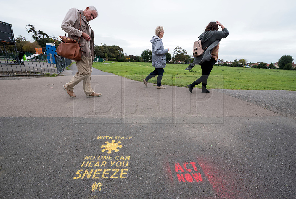 "© Licensed to London News Pictures; 09/09/2020; Clevedon, UK. Stencils are seen on the pathways by the Marine Lake advising people to keep social distancing during the coronavirus covid-19 pandemic. The stencils by North Somerset Council with their logo refer to cultural memes such as Star Trek ""Space the final frontier"", the film Alien ""In Space no one can hear you sneeze"", the song ""Don't Stand So Close To Me"" by the Police and the world war one recruitment poster ""North Somerset needs you to keep your distance"". Other stencils have been added referring to the climate crisis and global warming. Photo credit: Simon Chapman/LNP."