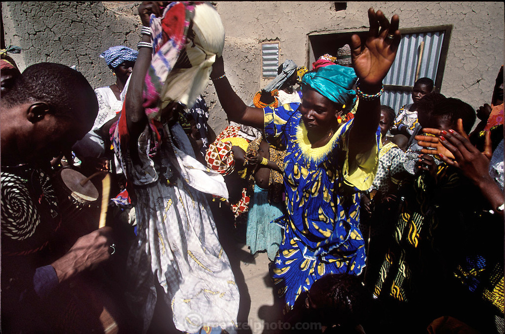 (MODEL RELEASED IMAGE). Pama Kondo (center, in blue) at the wedding celebration of her daughter Pai. (Supporting image from the project Hungry Planet: What the World Eats.) The Natomo family of Kouakourou, Mali, is one of the thirty families featured, with a weeks' worth of food, in the book Hungry Planet: What the World Eats.