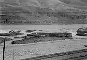 9305-B7385-4. Views of Celilo Falls before the permanent innundation. All the equipment and lumber scaffolds used for cable car transport have been stripped from the rocks. October 5, 1956. The channel on the left is between Papoose island (left) and Standing island (to its right, center foreground). The island behind Standing is Chief. Further back on the left is the tip of Big island and the Albert Brothers islands. On the extreme right is Chinook rock and behind it is Horseshoe falls and the Oregon shore.