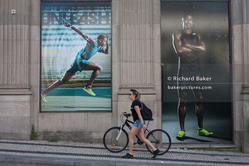A young woman pushes her bike up a steep hill, beneath the posters of athletes advertising sports clothing using the word Unleash as its slogan, on 20th July, in Porto, Portugal. (Photo by Richard Baker / In Pictures via Getty Images)