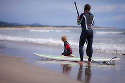 Father with his son paddleboarding on the beach, Viana do Castelo, Norte Region, Portugal