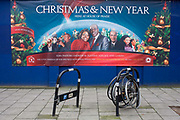 A banner for the black church House of Praise with abandoned and locked bicycle wheels in Walworth, south London. Church members and officials stare out at us in this PR poster on south London's Walworth Road known for its local shops and many black churches housed in all manner of buildings. The central couple are named as Olayemi and Andrew Adeleke, a husband and wife pastor who also sell religious books online. Other worshippers are seen to their left and right, visitors to this 'Redeemed Christian Church of God' as seen on the label far right.