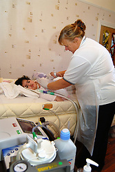 A Community Nurse changes the position of a profoundly disabled child;in her bed at home; Bradford, Children's community Nursing Team