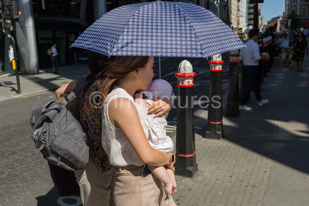 A mother carries her child beneath an umbrella during the 2018 heatwave in the City of London, the capitals historic financial district, on 2nd August 2018, in London, England.