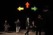 Large arrows coloured red, green and yellow point north, west and east - or up, right and left - in three directions, to offer directions to seminars for accountants during their annual Academy Day held for 3,000 of company London employees at Excel in London's Docklands, England. The people are either confidently pacing forward, standing still to seek guidance or simply spontaneously emerging from the shadows to a brighter future, a moment when freedom of choice is offered and the road ahead dictates their fate. It is a scene of corporate theatre and each employee will attend this fair where motivational pep-talks from executives, outside speakers and gurus will talk to large groups of personnel so their presence on this day away from the office is vital for the year's business ahead.