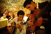 "The two guitarists fine tuning their instruments at the restaurant ""Mesa de Frades"", an old chapel in Alfama typical neighborhood"