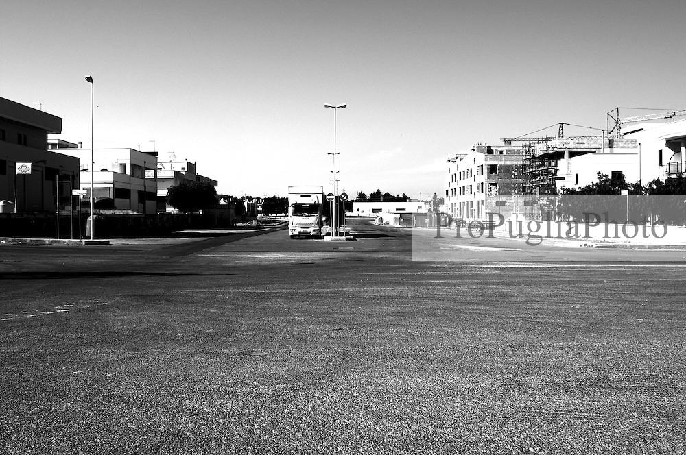 Camion parcheggiato nel piazzale antistante l'isola ecologica di Ostuni, presso la zona artigianale. Sullo sfondo alcune delle tante case in costruzione