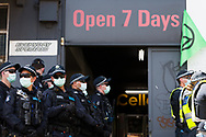 Police stand near a bottle shop during an Extinction Rebellion protest in Melbourne.  A small group of climate protesters marched from Flagstaff Gardens to The Queen Victoria Market and ending with two individuals gluing themselves together, and then glued themselves to Victoria Avenue outside of the Market. This comes as 5 new COVID-19 cases were uncovered in Melbourne's revamped Hotel Quarantine, breaking almost 40 days of virus free days. (Photo by Dave Hewison/Speed Media)