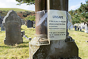 A notice addressed to the family whose gravestone is somehow damaged and requiring unspecified repairs before being laid horizontally on the ground, on 4th October 2021, in Llandudno, Gwynedd, Wales.
