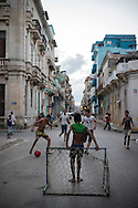 Neighborhood boys play a game of soccer at dusk on a city street in Centro Habana. When a vehicle needs to pass, the game is paused and goals briefly set to the side.