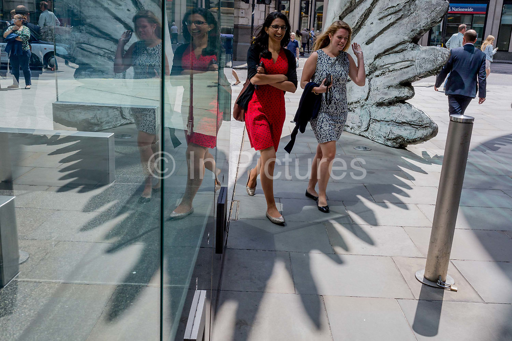Two young city worker women walk past the sculpture entitled City Wing on Threadneedle Street in the City of London, the capitals financial district aka the Square Mile, on 11th July 2019, in London, England. City Wing is by the artist Christopher Le Brun. The ten-metre-tall bronze sculpture is by President of the Royal Academy of Arts, Christopher Le Brun, commissioned by Hammerson in 2009. It is called 'The City Wing' and has been cast by Morris Singer Art Founders, reputedly the oldest fine art foundry in the world.
