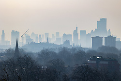 © Licensed to London News Pictures. 31/03/2021. London, UK. Members of the public enjoy an early morning misty sunrise over London from Primrose Hill in North West London as weather forecasters predict another warm day with highs of 23c in the South East. Photo credit: Alex Lentati/LNP
