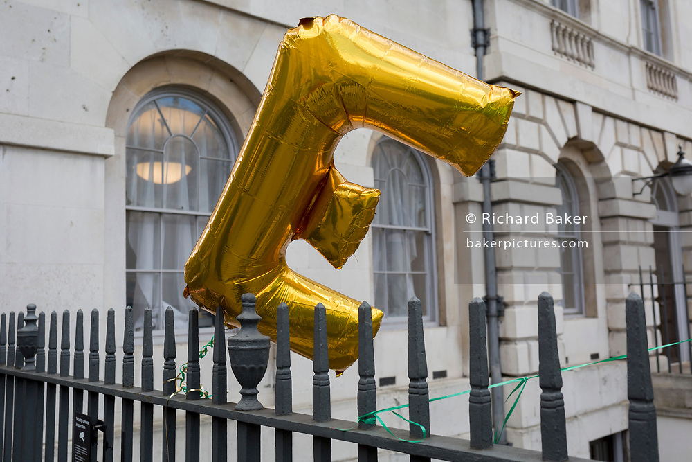 An E balloon (representing the concept of remaining in Europe) blows in the wind on railings during a pro-EU brexit protest opposite Parliament, on 11th March 2019, in Westminster, London, England.
