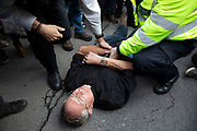 Extinction Rebellion climate change activist and priest lies down in Whitehall and then arrested by police as sites around Westminster are blocked on 8th October 2019 in London, England, United Kingdom. Extinction Rebellion is a climate group started in 2018 and has gained a huge following of people committed to peaceful protests. These protests are highlighting that the government is not doing enough to avoid catastrophic climate change and to demand the government take radical action to save the planet.
