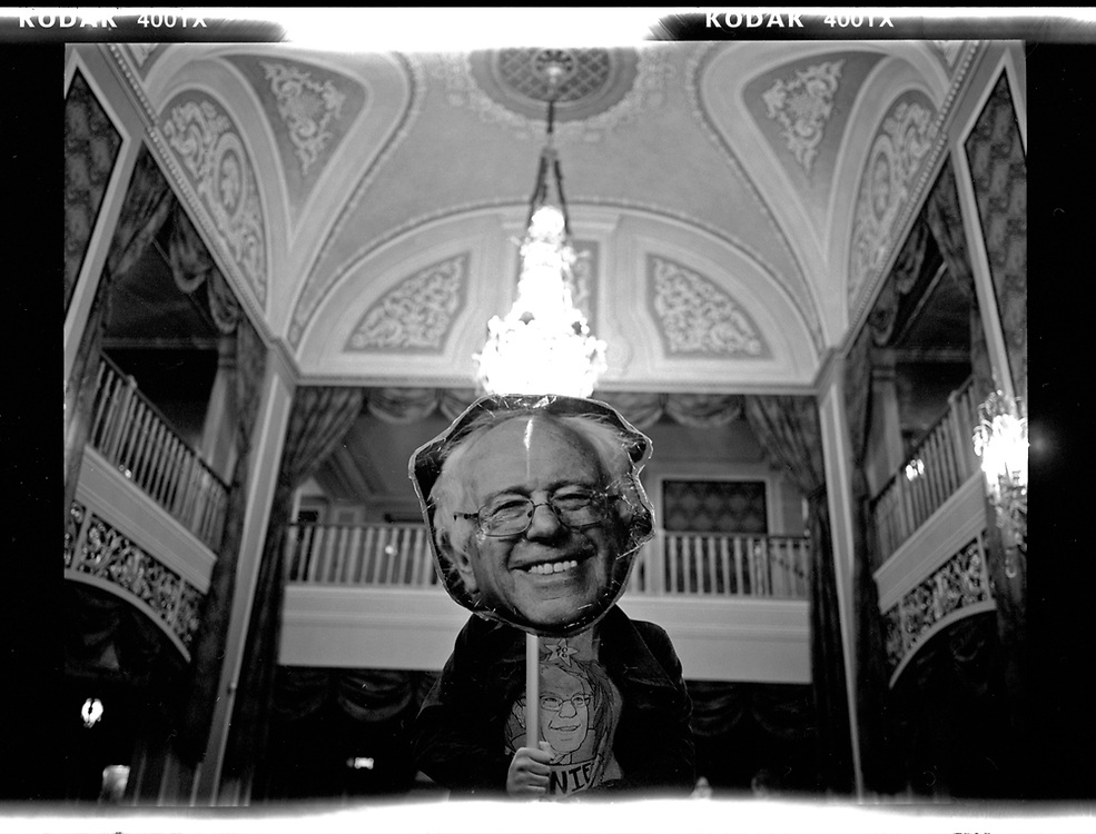 Katelyn Trestle, a supporter of U.S. Democratic presidential candidate Bernie Sanders, holds a giant cutout of Sanders' head at a campaign event at the Orpheum Theatre in Sioux City, Iowa. © Photo by Jim Young