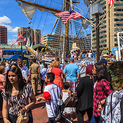 Baltimore, MD, USA - June 16, 2012: Visitors walk past the large ships on a summer day in the Inner Harbor of the City of Baltimore, Maryland.