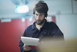 Young male engineer wearing headset and working in an industrial plant, Freiburg im Breisgau, Baden-Wuerttemberg, Germany