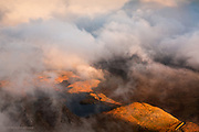 Banks of cloud roll in from the Irish Sea at sunset, and curl over the top of the Nantlle Ridge in Snowdonia and over Rhyd Ddu and the lakes of Llyn y Dywarchen and Llyn y Gader, Snowdonia, North Wales. Taken from a lower ridge of Mynydd Mawr