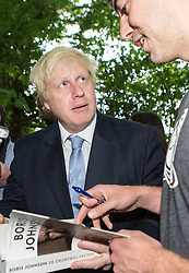© Licensed to London News Pictures. 30/07/2015. London, UK. The Mayor of London and MP for Uxbridge and South Ruislip Boris Johnson signs a copy of his book during a visit to the Wide Horizons Environment Centre in Bexley where he explored their new outdoor learning centre which was built by an 'army of volunteers' on a once derelict site. Photo credit : James Gourley/LNP