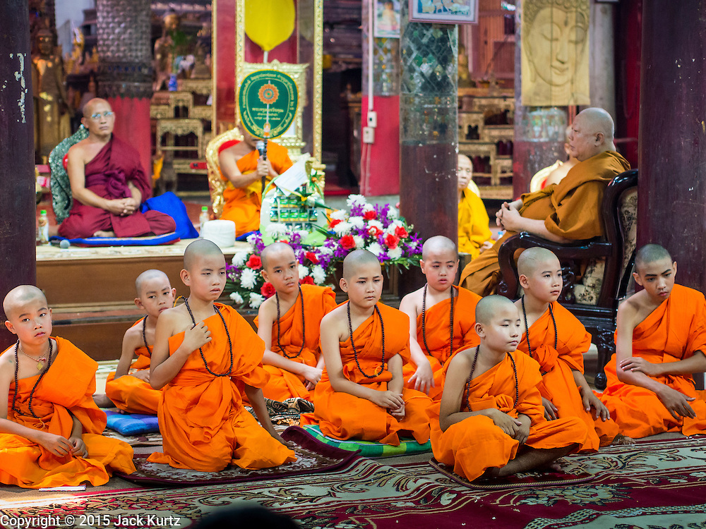 """06 APRIL 2015 - CHIANG MAI, CHIANG MAI, THAILAND: Newly ordained Buddhist novices after their first chanting service as monks during their ordination ceremony on the last day of the three day long Poi Song Long Festival in Chiang Mai. The Poi Sang Long Festival (also called Poy Sang Long) is an ordination ceremony for Tai (also and commonly called Shan, though they prefer Tai) boys in the Shan State of Myanmar (Burma) and in Shan communities in western Thailand. Most Tai boys go into the monastery as novice monks at some point between the ages of seven and fourteen. This year seven boys were ordained at the Poi Sang Long ceremony at Wat Pa Pao in Chiang Mai. Poy Song Long is Tai (Shan) for """"Festival of the Jewel (or Crystal) Sons.   PHOTO BY JACK KURTZ"""