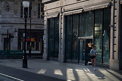 © Licensed to London News Pictures. 08/11/2020. London, UK. A woman jogs past a closed branch of All Bar One on a quiet Regent Street in Central London. A national lockdown has been put in place in an attempt to fight a second wave of the COVID-19 strain of Coronavirus. Photo credit: George Cracknell Wright/LNP