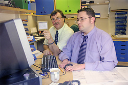 Man with disability; who is wheelchair user; and colleague working at computer in office,