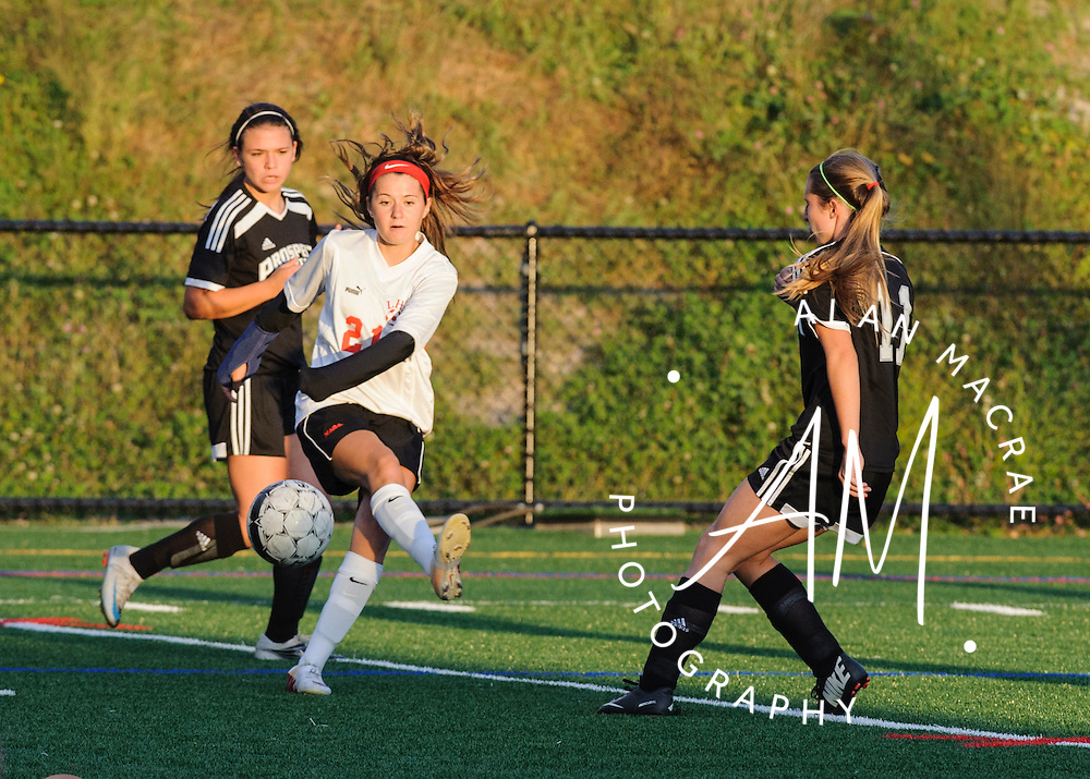 Laconia's Kailey Nute kicks the ball away from a pair of Prospect Mountain offensement during Tuesday's match at Laconia's Fitzgerald Field.  (Alan MacRae/for the Laconia Daily Sun)