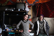 A Roma family living in a squat in the snow in one of the largest Roma encampments 'bidounvilles' outside Paris. Winter, Sarcelles, Paris suburbs, France<br /><br />Eastern european Roma migrants, often from Romania and Bulgaria, searching for better opportunities, they move near to western european cities. They typically are poor and live in squats, here around the periphery of Paris, in the suburbs 'banlieu' where they typically build ramshackle homes from recycled wooden panels and corrugated iron, or sometimes benders made from branches covered in tarpaulins. They live in woods and forest, industrial estates or derelict buildings. Life is especially difficult for them in the harsh conditions of winter and rain. Most of these camps get destroyed by police and Roma are eventually evicted, some deported back home or moving on to build another home. They often survive by recycling metal and electronic goods, selling recycled clothes and objects they find in trash bins, or through begging or playing music on the city streets or inside metro stations. Paris, France