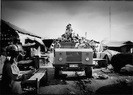 Truck loaded down negotiates the narrow road that is often inundated by the waters of Tonle Sap, which functioned this day as a makeshift market, Chong Kneas, Cambodia.