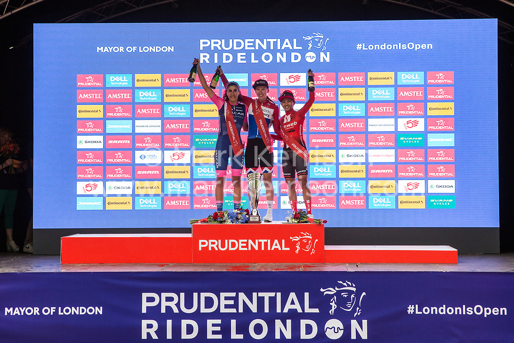 London, UK. 3 August, 2019. Elisa Balsamo (l, Valcar Cylance Cycling), Lorena Wiebes (c, Parkhotel Valkenburg) and Coryn Rivera (r, Team Sunweb) receive their awards for finishing second, first and third respectively in the Prudential RideLondon Classique. The Classique, which is the richest one-day women's race in the world, covers 20 laps of a tight circuit of 3.4 kilometres around St James's Park and Constitution Hill.