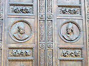 Detail from the main portal doors from the Basilica di Santa Maria del Fiore, (more commonly called the 'Duomo'). Florence, Italy. Three huge bronze doors, adorned with scenes from the life of Madonna. They date from 1899 to 1903. Around the doors are multiple works of art: Mosaics by Niccolò Barabino, a half-relief by Tito Sarrocchi, and a series of niches and busts. The duomo was started in 1296 based on Arnolfo di Cambio's design, but was not complete until 1436 when Filippo Brunelleschi engineered the dome. One of Italy's largest churches.