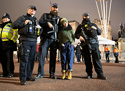 © Licensed to London News Pictures. 31/12/2018. London, UK. A tourist poses for a photograph with armed police on duty in The Mall as people begin to celebrate New Year's Eve in central London.  Over 100,000 people are attending London's ticketed fireworks display on the banks of the River Thames for New Year's Eve tonight. Photo credit: Peter Macdiarmid/LNP