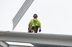 Steel Worker as a roof segment being lowered to his position during Steel Erection at the Central Connecticut State University New Academic Building Construction.