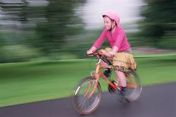 Young girl wearing bike helmet riding bike through wood,
